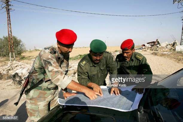 Palestinian Security officers look at a map as they survey and inspect an area they will secure next week near the Israeli Jewish settlement of Morag...