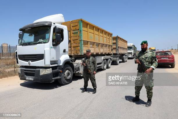 Palestinian security officers stand next to Palestinian trucks at a checkpoint before heading to the Israeli side at the Kerem Shalom crossing in...