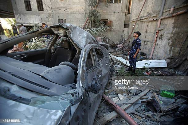 Palestinian security official stands at the site of an Israeli airstrike in Khan Younis southern Gaza Strip on July 8 2014 Seven Palestinians were...