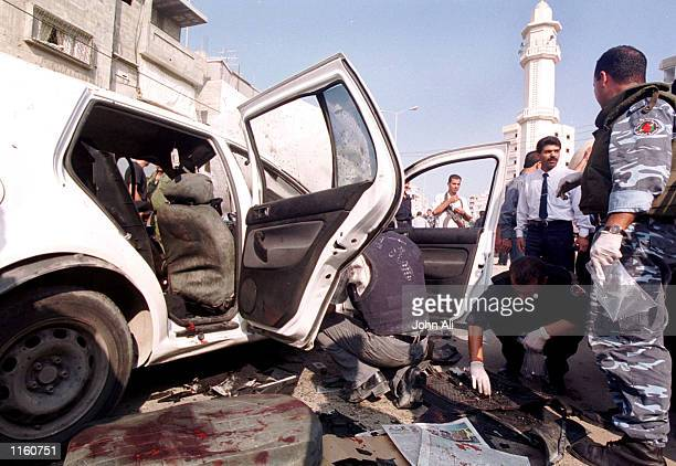 Palestinian security officials inspect wreckage following the death of Col. Tayser Khattab, a top aide to the Palestinian intelligence chief, who was...