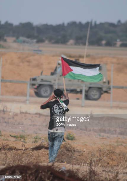 Palestinian seen holding a flag during the protest Palestinians clash with the Israeli forces during a protest calling for lifting the Israeli...