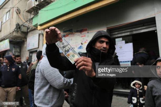 Palestinian seen holding a hundred dollar bill after receiving Qatari assistance at the post office in Gaza strip Palestinians receive first phase of...