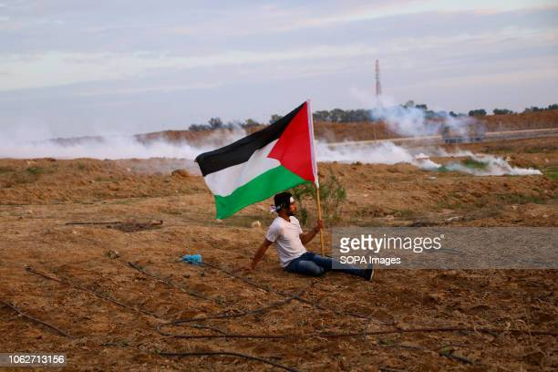 Palestinian seen on the ground raising high a Palestinian flag during the clashes Clashes between Palestinian citizens and Zionist occupation forces...