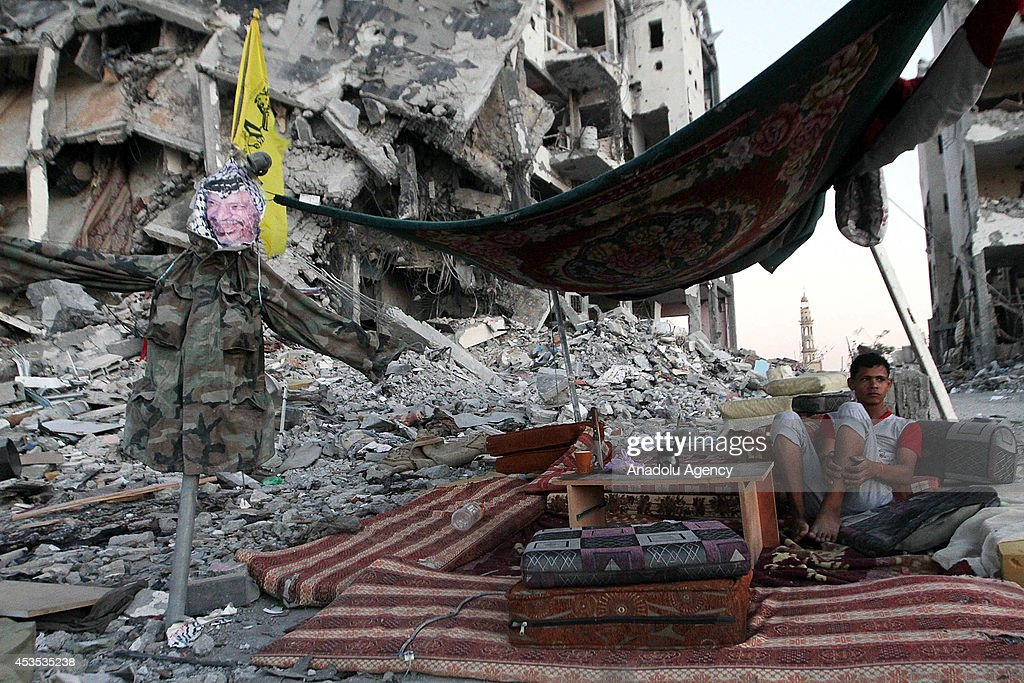 A Palestinian sets up a scrappy tent as Palestinians get back to Beit Lahia to inspect their houses destroyed by Israeli army and collect their leftover belongings during a 72-hour humanitarian ceasefire in Gaza on August 12, 2014.