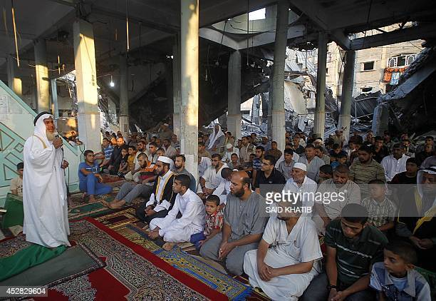 A Palestinian Sheikh leads a prayer on July 28 on the first day of Eid alFitr at the heavily damaged AlFaruq mosque destroyed a week ago by an...