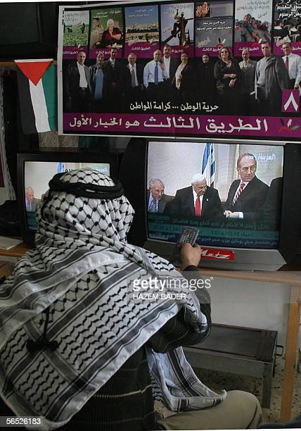Palestinian shopkeeper watches the news about Israeli Prime Minister Ariel Sharon's grave state of health 05 January 2006 in the West Bank town of...