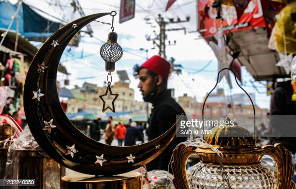 Palestinian shopkeepers displays lanterns and other decorative items ahead of the fasting month of Ramadan, in the town of Khan Yunis in the southern...