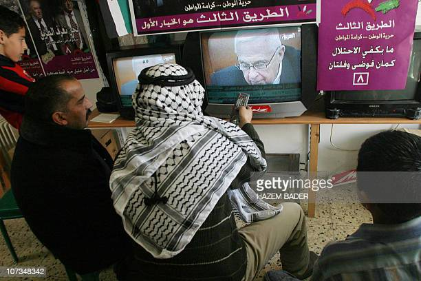 Palestinian shopkeepers watch the news about Israeli Prime Minister Ariel Sharon's grave state of health 05 January 2006 in the West Bank town of...