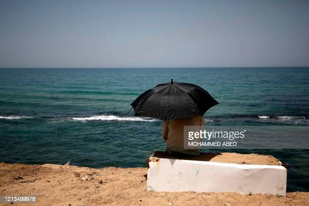 A Palestinian sits beneath an umbrella by the shoreline of a beach in Gaza City on May 18 2020 Across the Mediterranean with its tantalising beaches...