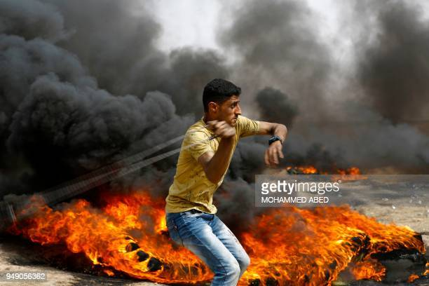 Palestinian slings a shot by burning tires during clashes with Israeli forces across the border, following a demonstration calling for the right to...