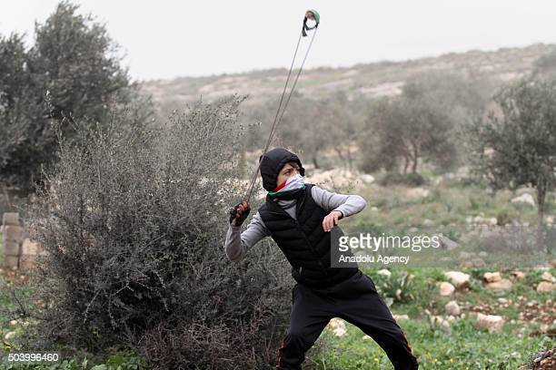 Palestinian slings stones to Israeli security forces during a protest against expropriation of their lands by Israel at Kafr Qaddum village in Nablus...