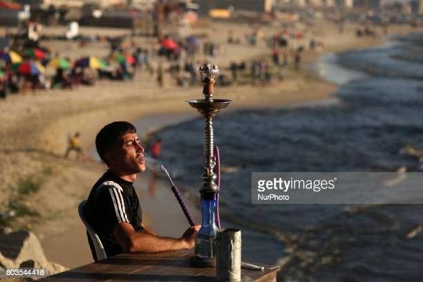 A Palestinian smokes shisha or hookah as they try to escape the heat of a hot summer day on Gaza beach as temperatures reached 40C in the Gaza City...