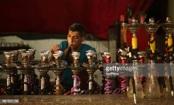 A Palestinian smokes shisha or hookah at a Royal Plaza Cofee shop in Gaza City on May 9 2017