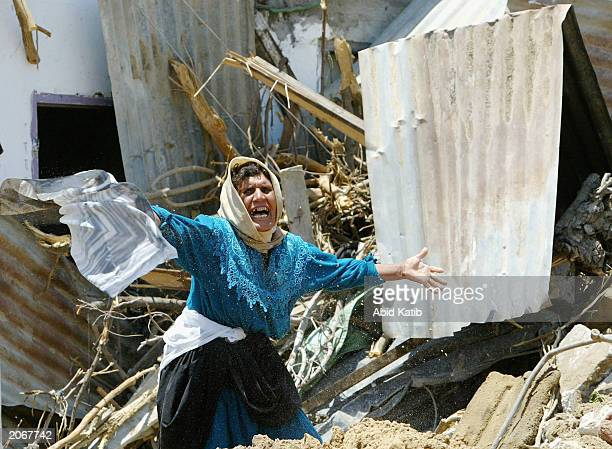 Palestinian Sobheah Abu Amshah cries in front her demolished house on June 9 2003 in Beit Hanon town in the northern Gaza Strip Israeli army troops...