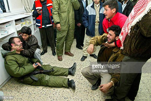 Palestinian solider and relative of one of two palestinian youths killed by israeli troops weep in the treatment room of the Nasser Hospital in Khan...