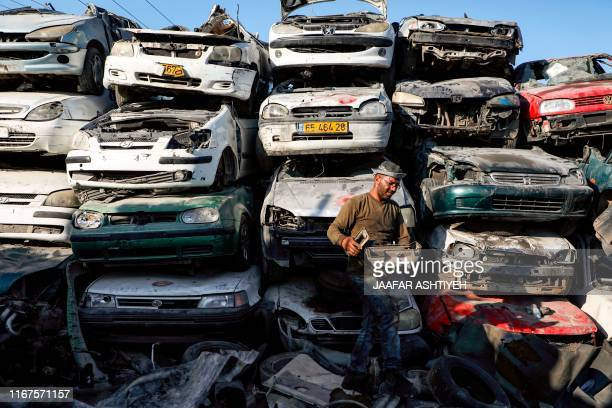 Palestinian spare parts dealer walks with a disassembled part past stacked car wrecks in a scrap yard at the Askar refugee camp east of Nablus in the...