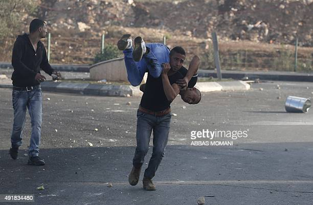 A Palestinian stone thrower carries an injured comrade after he was shot in the leg by Israeli security forces during clashes in Beit El near the...