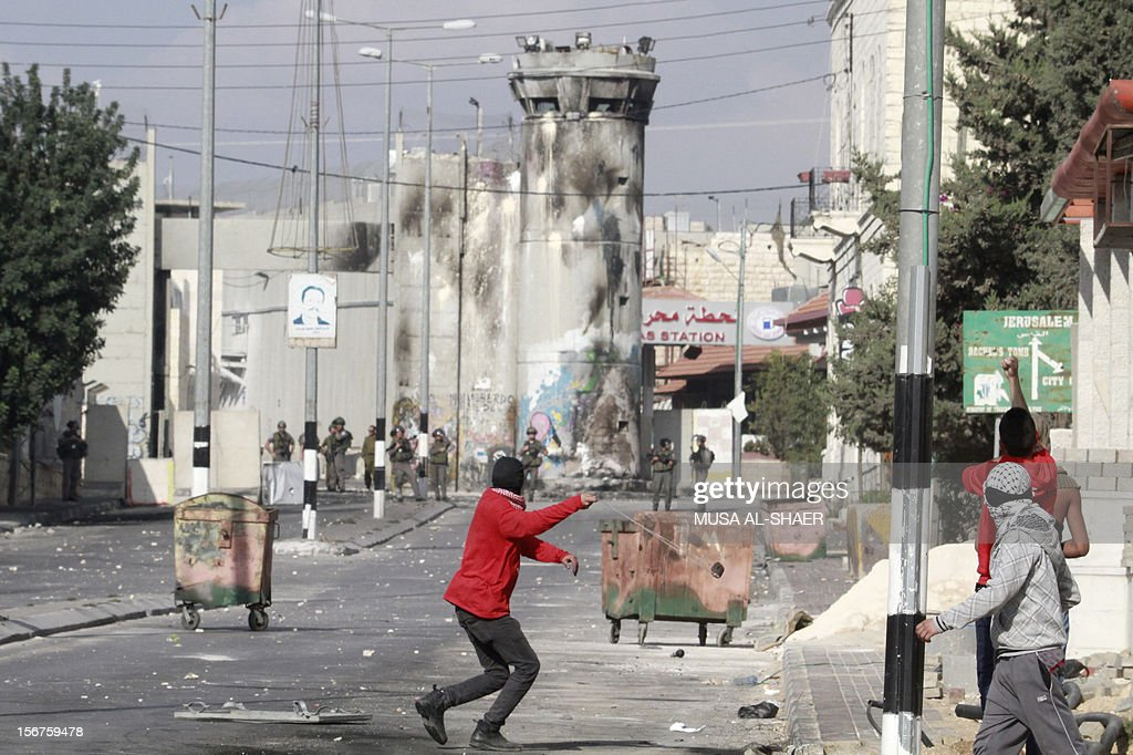 Palestinian stone throwers clash with Israeli security forces (back) in front of an Israeli army tower at the main entrance of the West Bank city of Bethlehem, on November 20, 2012. Palestinians clashed with Israeli security forces in the occupied West Bank as thousands marched demanding revenge for the killing of a protester the day before