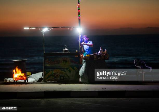 A Palestinian street vendor stands behind his stall in front of the beach in Gaza City during a power outage on June 11 2017 / AFP PHOTO / MAHMUD HAMS