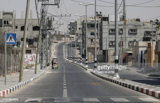 A Palestinian street vendor stands in an empty street during a general strike in the town of Rafah in the southern Gaza Strip on June 25 denouncing...