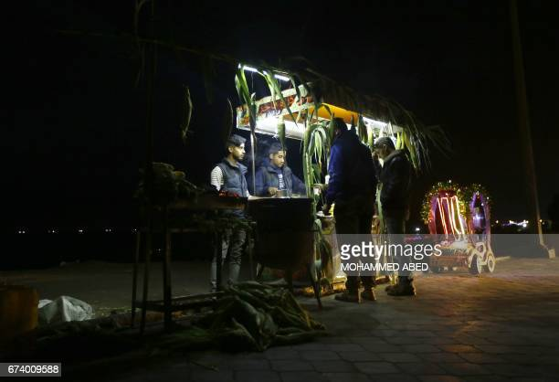 Palestinian street vendors use batterypowered lights as they sell corn during a power cut in Gaza City on April 27 2017 Hit by the bitter rivalry...