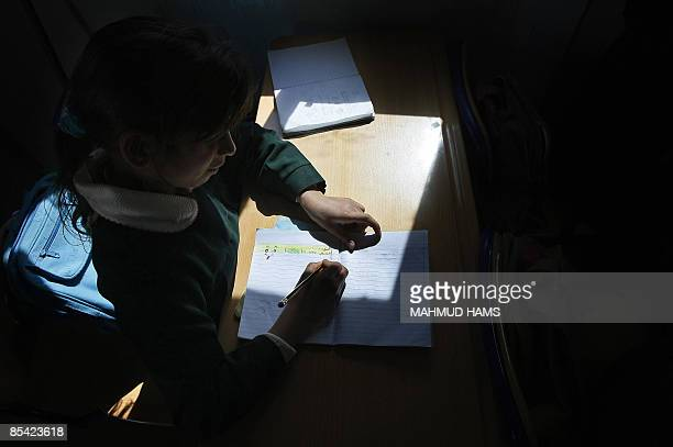 A Palestinian student writes in her notebook inside a modular classroom donated by the Dubaibased organisation 'Dubai Cares' at a school which was...