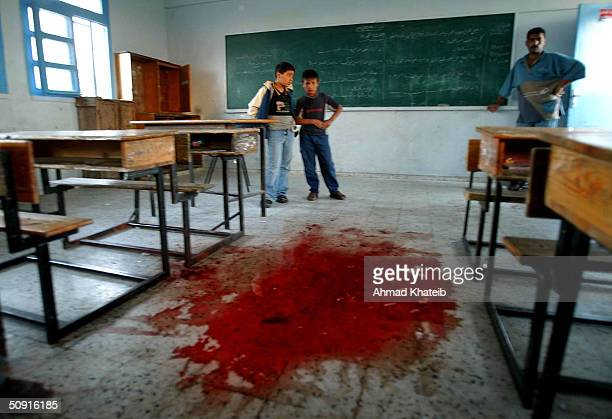 Palestinian students and a teacher look at a large pool of blood on the floor of the United Nations school June 1 2004 in the Tal Sultan section of...