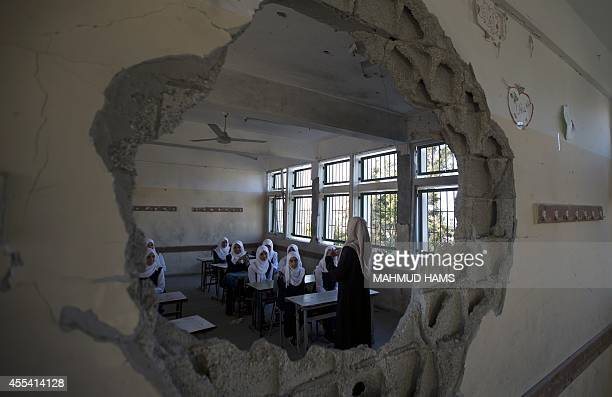 Palestinian students are seen through a damaged sitting in a classroom at a goverment school in the Shejaiya neighbourhood of Gaza City on September...