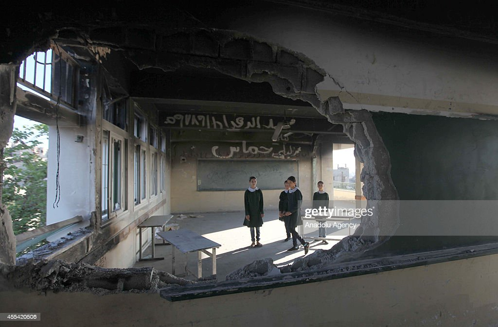 Palestinian students are seen through a damaged wall standing in a classroom at Abu Kris primary school in Gaza City, Gaza on September 14, 2014 on the first day of the new school year. Half a million children in Gaza start the new school year three weeks late as a result of the 50-day war between Israel and Palestinians that ended on August 26, 2014.