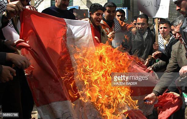 Palestinian students burn a Danish flag in the West Bank city of Hebron 20 February 2006 during a demonstration to protest against cartoons of the...