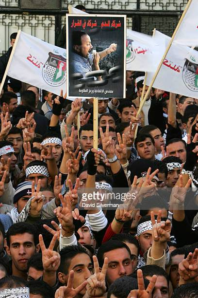 Palestinian students from the Fatah faction of the PLO surround a poster of Marwan Barghouti as they celebrate their victory in student elections...