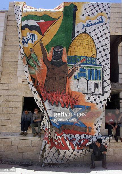 Palestinian students gather around a huge intifada or uprising painting 04 June 2003 in the West Bank city of Hebron The students were protesting to...