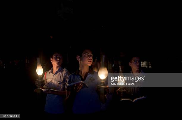 Palestinian students light candles to study during a protest against power cuts in Gaza City on November 12 2013 A shortage of fuel halted the...