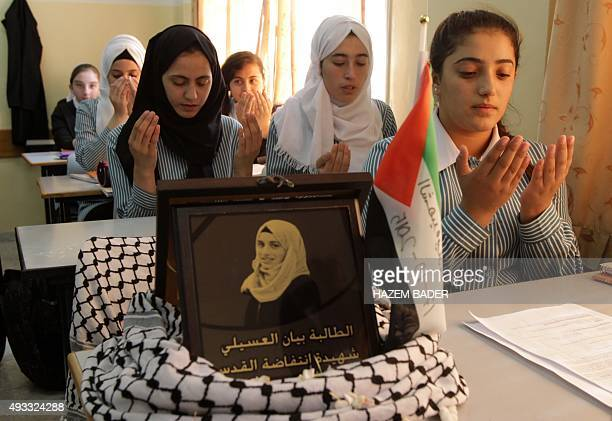Palestinian students pray in a classroom in the Israeli occupied West Bank town of Hebron on October 19 2015 next to an empty chair of their former...