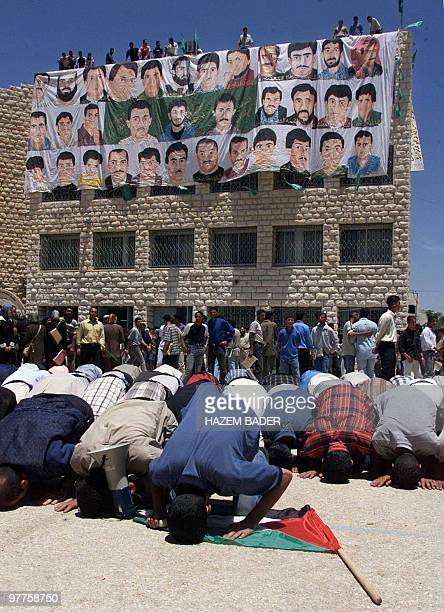 Palestinian students pray in front of a huge banner showing hand-painted portraits of Palestinians killed during the intifada, or uprising, 04 June...