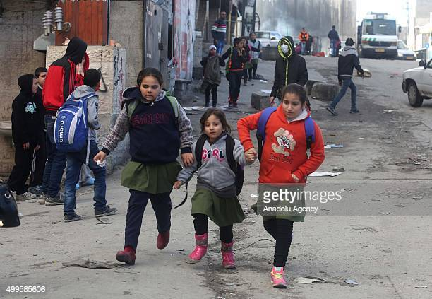 Palestinian students run towards their houses during a protest against the demolishment of Ibrahim ElAkkari's house in the Shuafat Refugee Camp in...