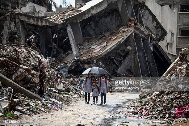 Palestinian students walk near the debris of destroyed houses which were destroyed in the Israeli airstrikes in Shujaiya neighborhood of Gaza City on...