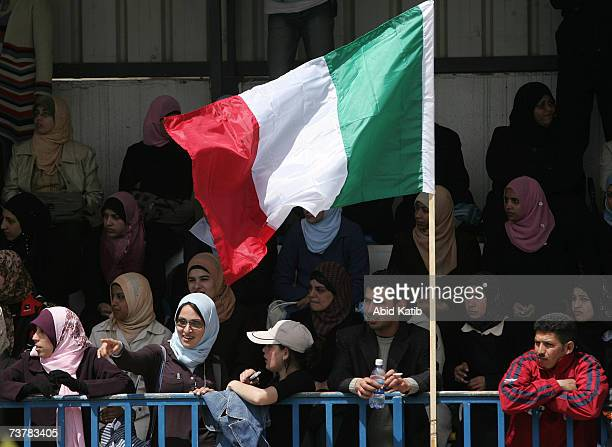 Palestinian students watch a soccer match beside an Italian flag between the women's team of AlAqsa University Gaza City and the Italian women's team...