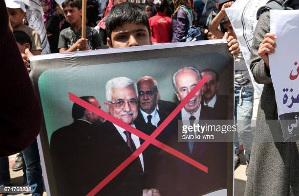 Palestinian supporter of AlAhrar movement a network of former Fatah operatives holds a crossed out poster depicting Palestinian president Mahmud...