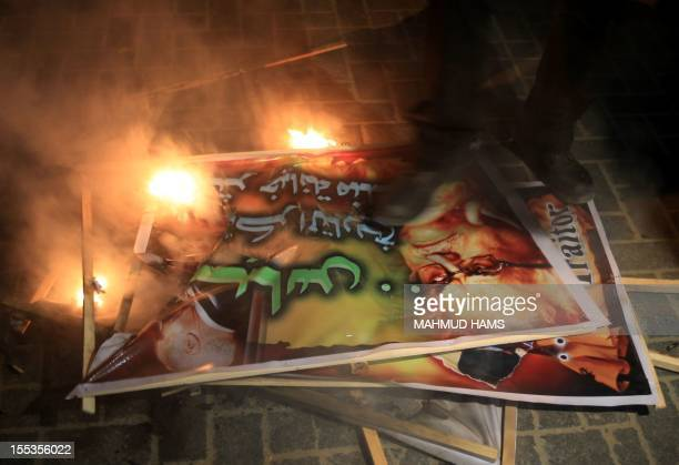 Palestinian supporter of Hamas movement steps on burning portraits of the Palestinian Authority president Mahmud Abbas, during a demonstration in...