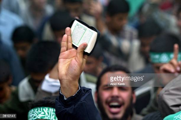 Palestinian supporter of the Islamic Hamas movement holds the Kuran holy book as the supporters shout anti-Israel slogans during a demonstration in...