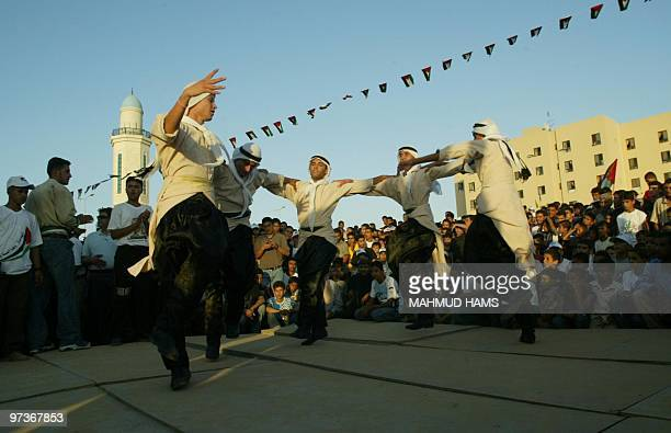 Palestinian supporters of Fatah movement perform a traditional dance as they celebrate the Israeli pullout of the Jewish settlements in Beit Lahia...