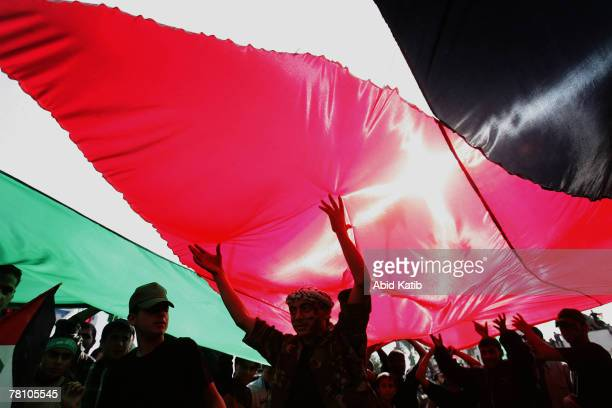 Palestinian supporters of Hamas and Islamic Jihad movements stand under the Palestinian flag as they protest against this week's Middle East peace...
