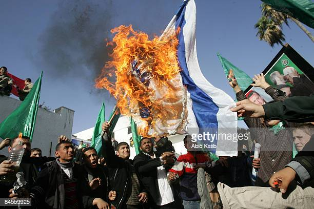 Palestinian supporters of Hamas burn an Israeli flag during a demonstration outside the destroyed parliament building on January 30 in Gaza City Gaza...