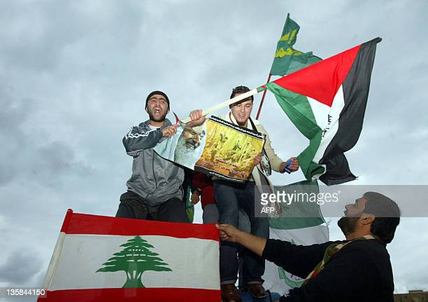 Palestinian supporters of Hamas hold up a Lebanese flag and a Palestinian flag with Islamic writing as they celebrate the landslide victory of the...