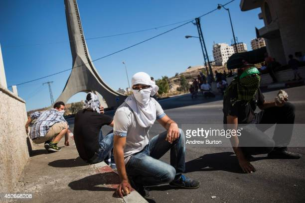 Palestinian supporters of Hamas take shelter while clashing with Israeli security forces on July 25 2014 near Ramallah West Bank As the Israeli...