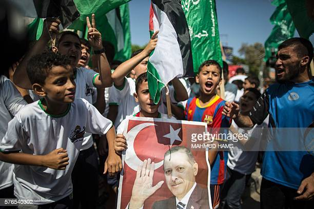 Palestinian supporters of the Hamas movement hold portraits of Turkish President Recep Tayyip Erdogan as they shout slogans against the military coup...