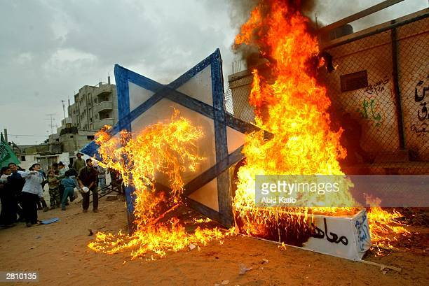 Palestinian supporters of the Islamic Hamas movement burn a Star of David and a coffin symbolizing the so-called Geneva Initiative peace plan during...