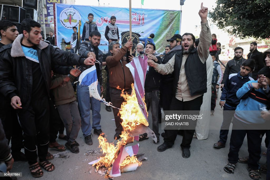 Palestinian supporters of the Islamic Jihad movement burn a US and an Israeli flag during a protest against the US president's decision to recognise Jerusalem as the capital of Israel, in the town of Rafah in the southern Gaza Strip, on January 12, 2018. /