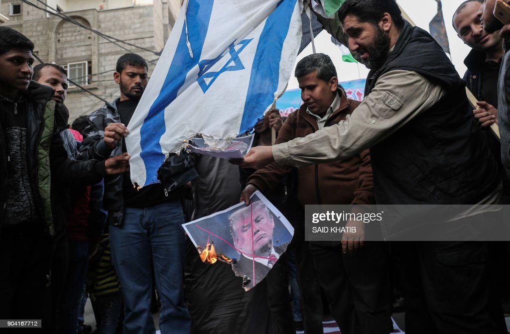 Palestinian supporters of the Islamic Jihad movement burn an Israeli flag and a portrait of US President Donald Trump during a protest against Trumps's decision to recognise Jerusalem as the capital of Israel, in the town of Rafah in the southern Gaza Strip, on January 12, 2018. /